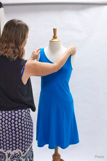 Woman styling dress on mannequin.