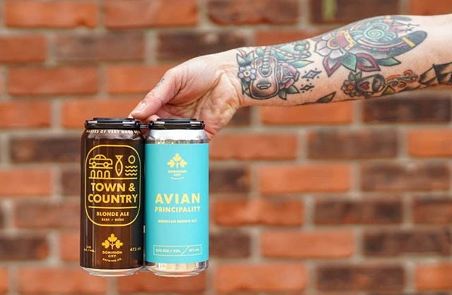 An outstretched tattooed arm and hand holding two cans of beer