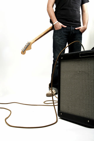 Neck-down shot of a guy with his electric guitar and amplifier