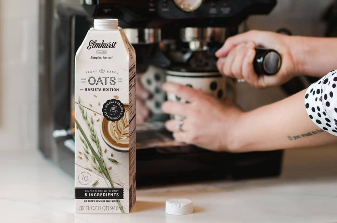 Elmhurst 1925 oat milk sitting on a counter next to a woman making an espresso