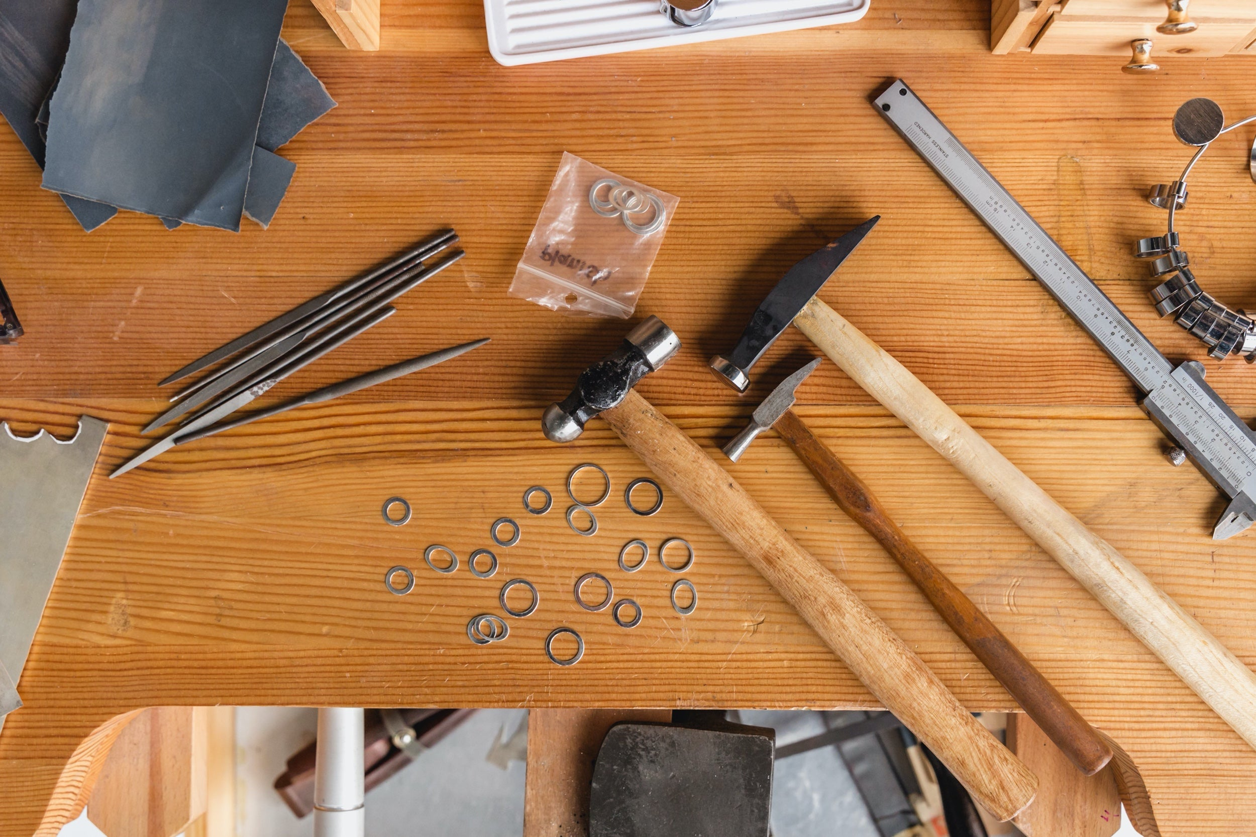 Overhead shot of a workspace covered in jewelry making tools