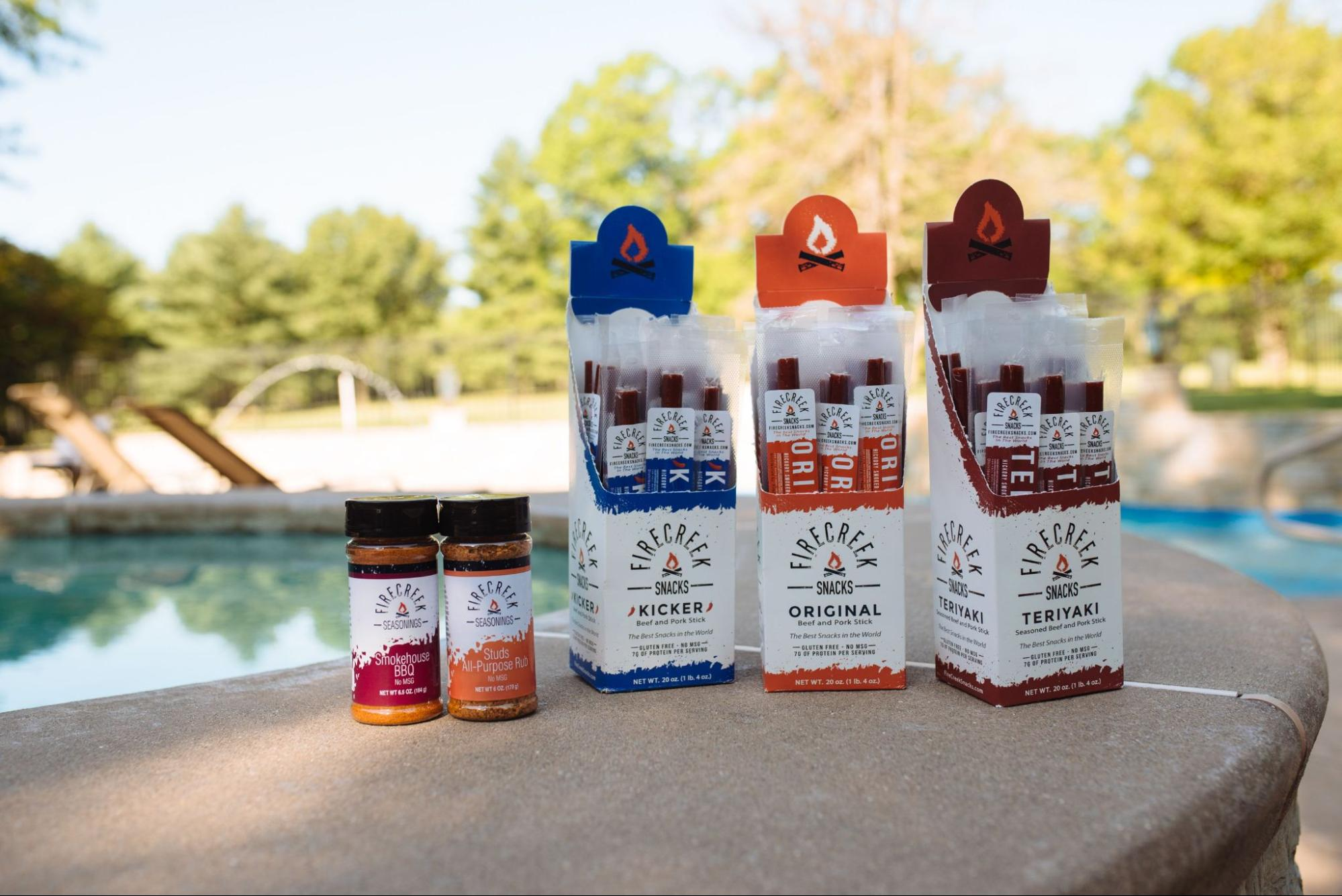 A selection of seasonings and jerky from FireCreek Snacks backdropped by a pool setting.