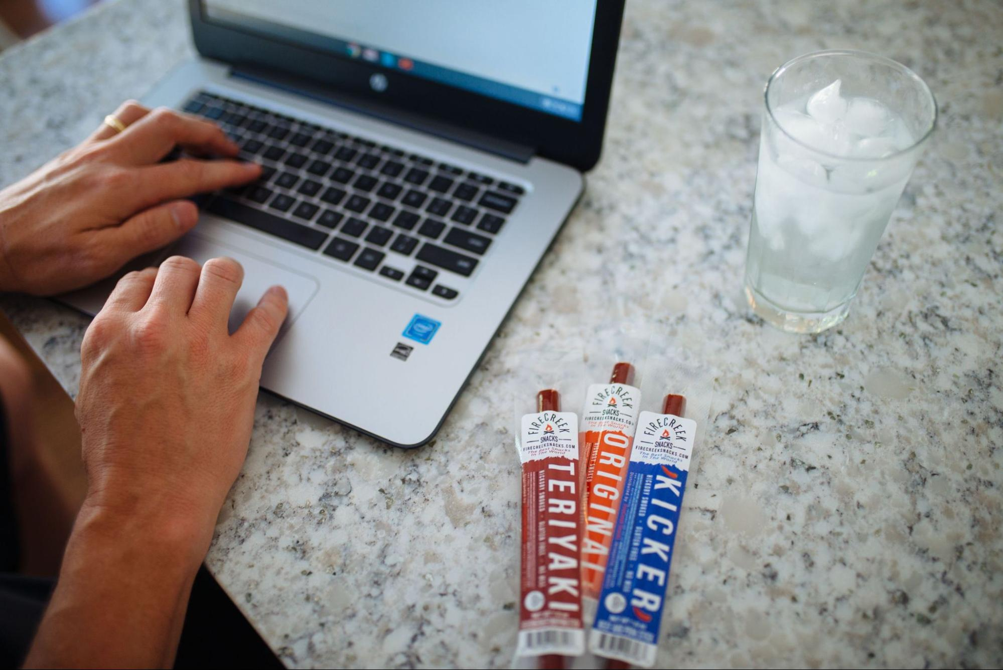 Three jerky from FireCreek Snacks on a marble countertop backdropped by a pair of hands typing on a laptop.