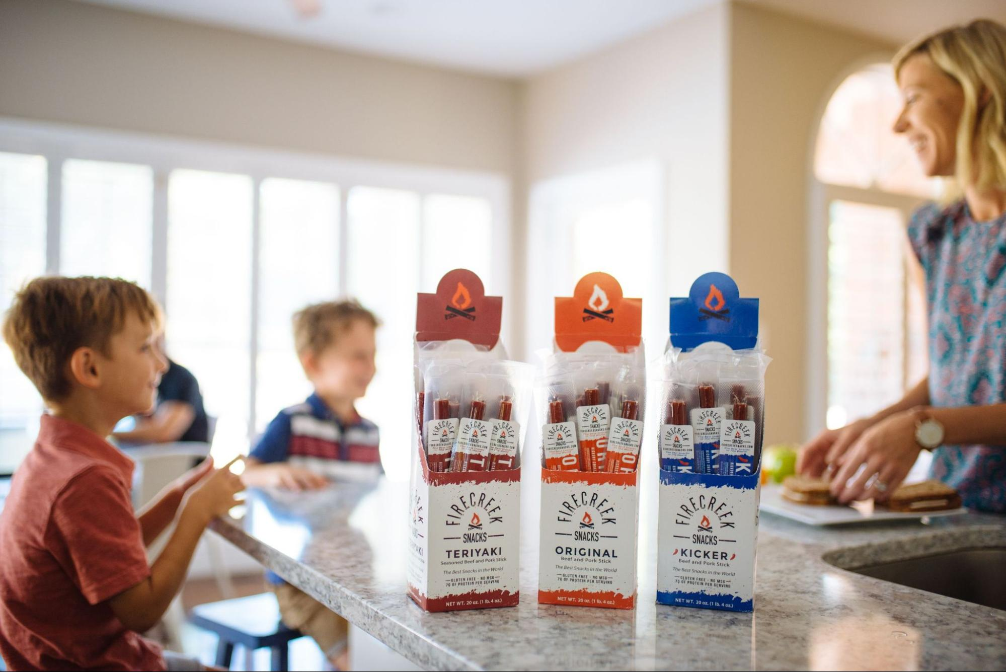 Three boxes of FireCreek Snacks jerky backdropped by a family within their kitchen.