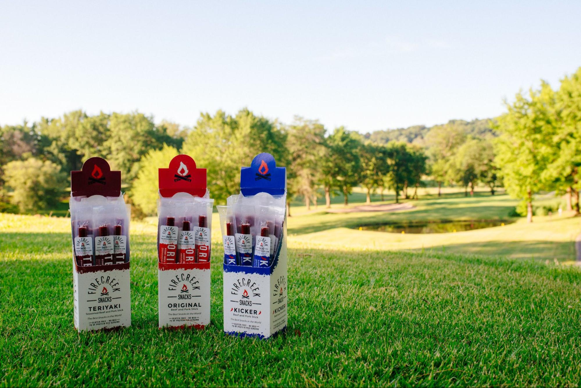 A set of different jerky from FireCreek Snacks backdropped by a park setting.