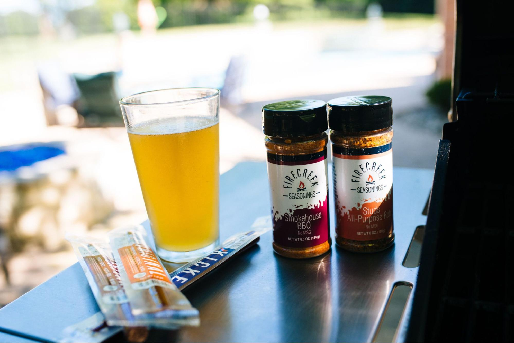 A duo of seasonings from FireCreek and some packs of jerky back dropped by a beverage.