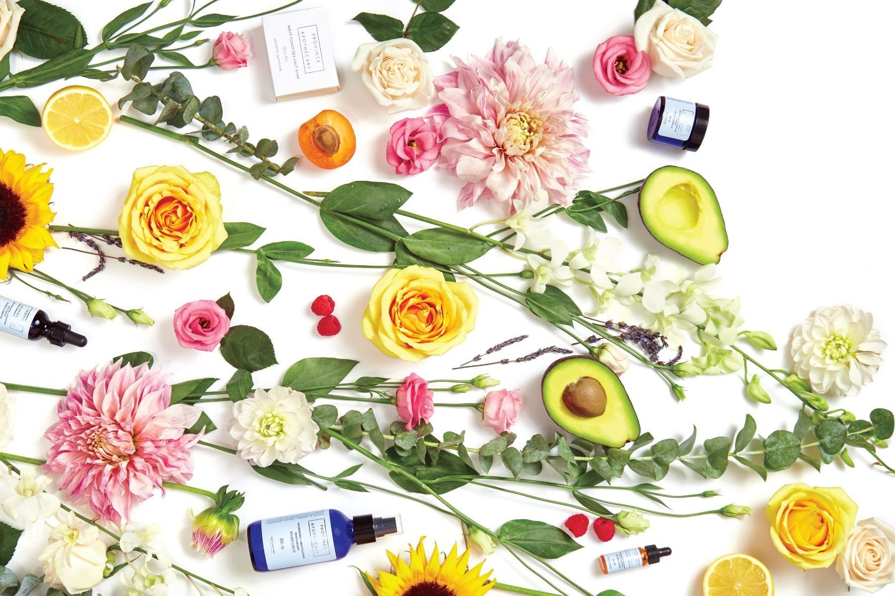 A flat lay of Province Apothecary products along with fresh flowers and other ingredients.