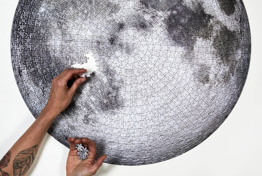 person's hands completing a puzzle of the moon