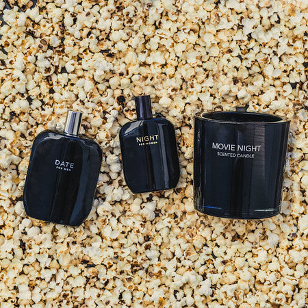 A few bottles of Fragrance One scents along with a scented candle backdropped by popcorn.