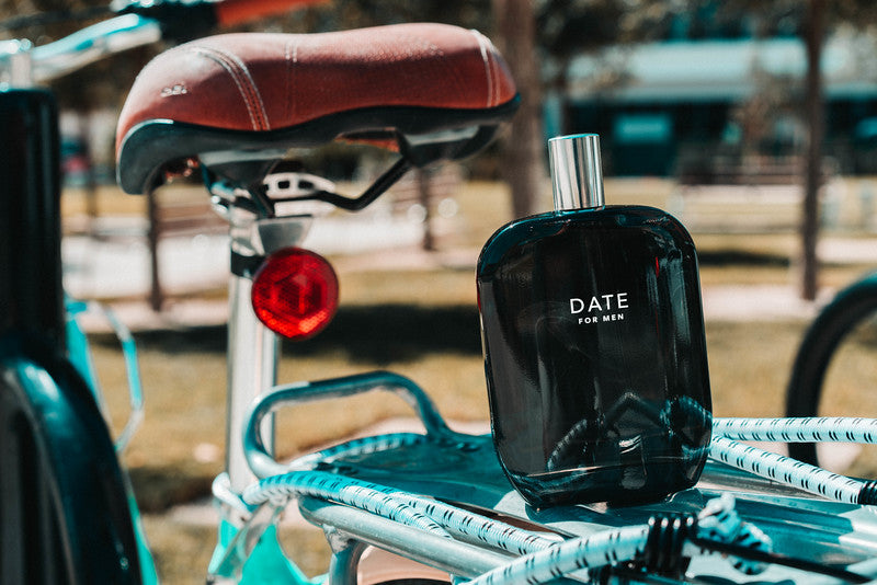 A bottle of Date for Men scent by Fragrance One on the back of a bicycle.