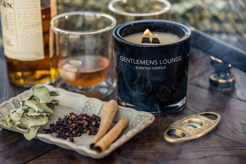 A scented candle made by Fragrance One set along with drinks, and dried ingredients on a tray.