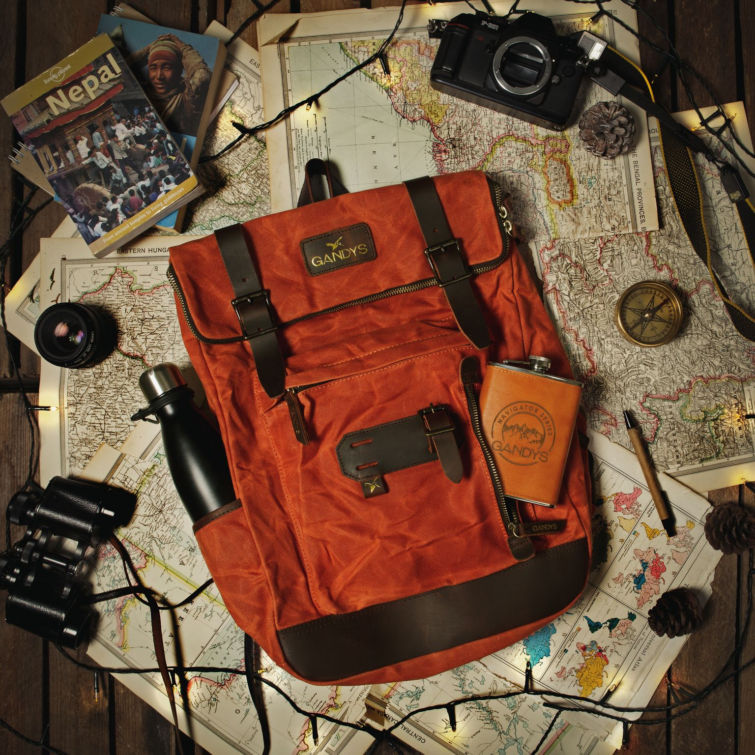 An orange Gandys backpack along with a flask is backdropped by maps and a compass in a flatlay.