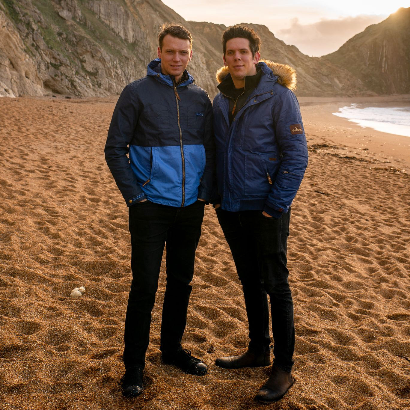 Rob and Paul Forkan the founders of Gandys International on a beach backdropped by mountains.