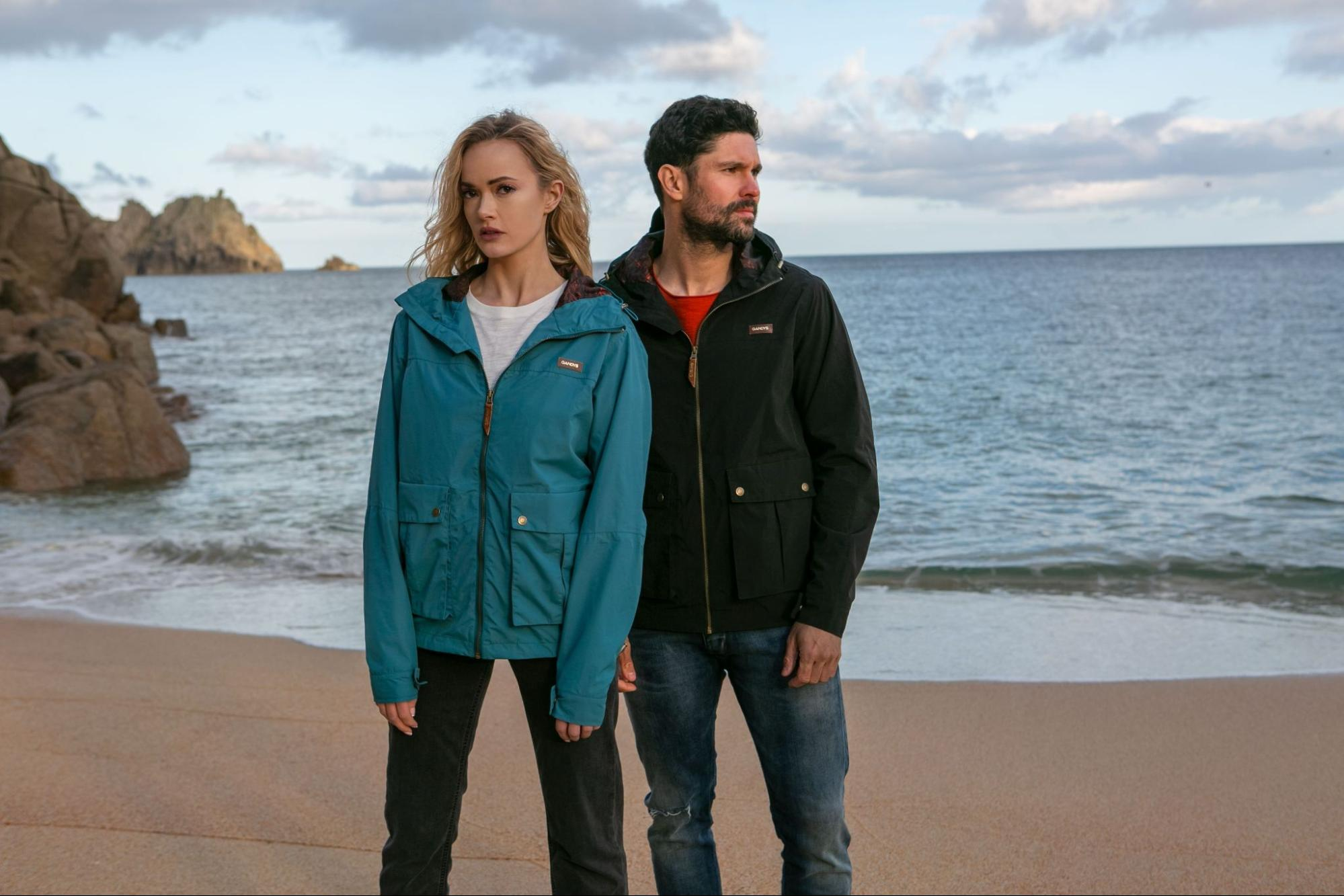 A pair of models in Gandys clothing on a beach setting backdropped by mountains.