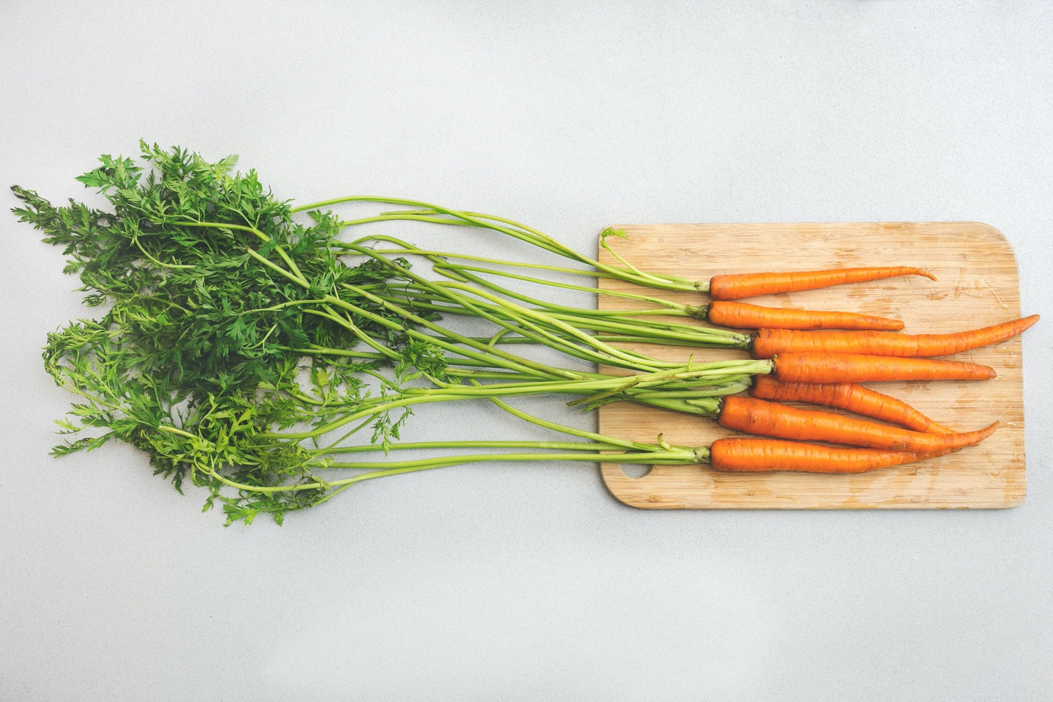 A bunch of garden carrots on top of a wood cutting board