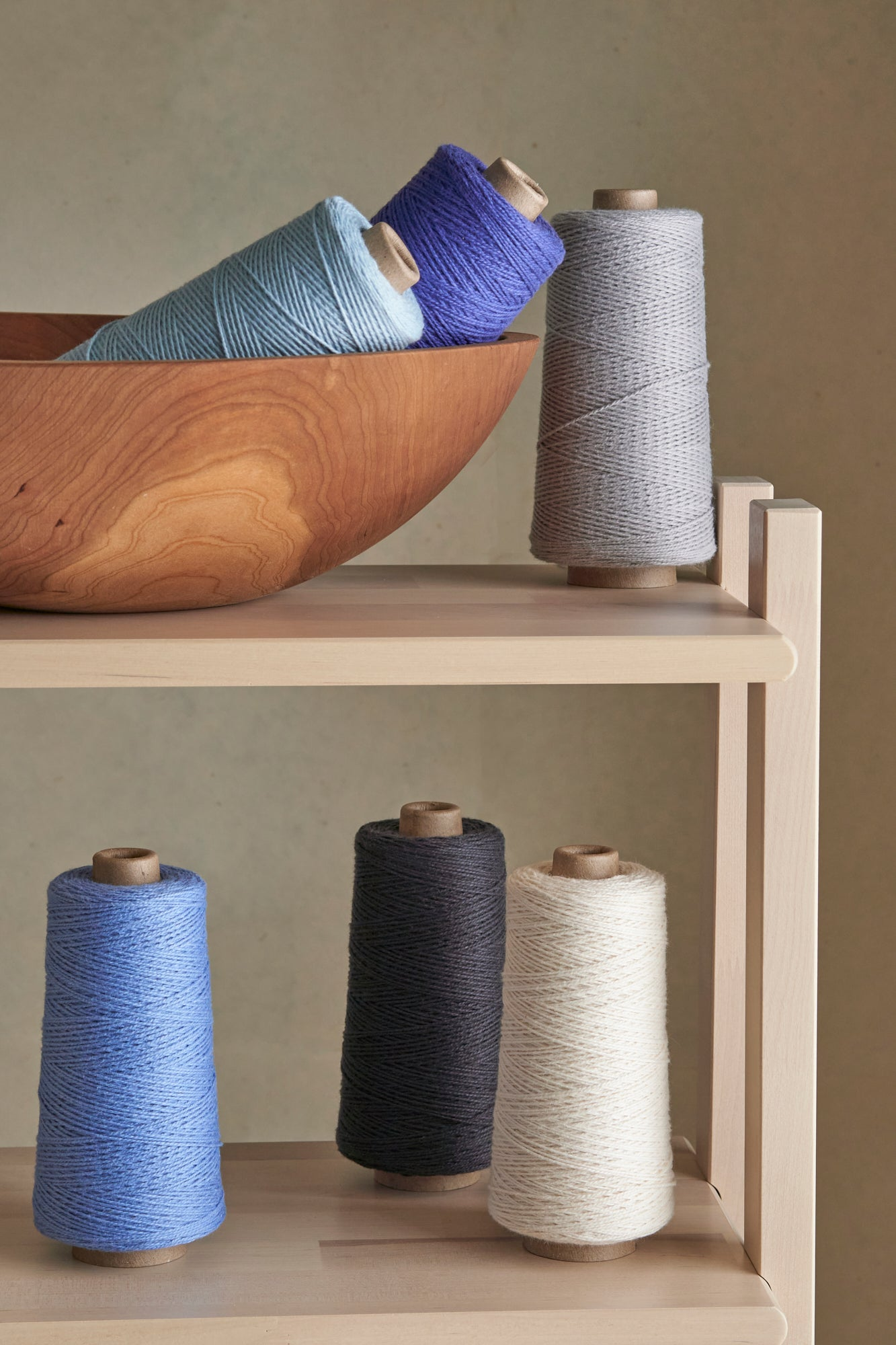 A set of cool toned yarns displayed on a wooden shelf.