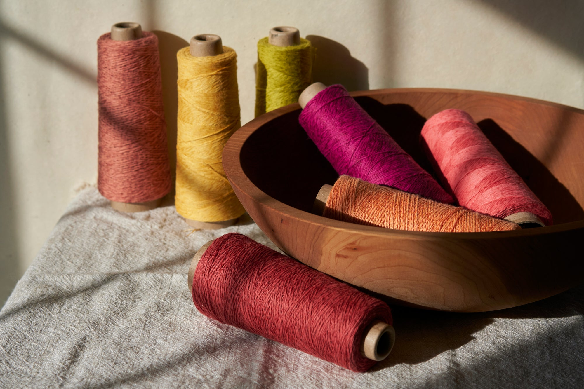 A collection of threads placed in a wooden bowl backdropped by more threads.