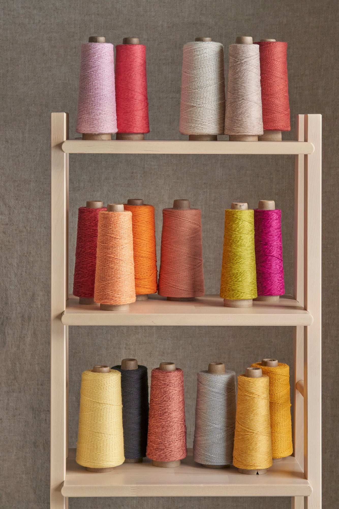 An array of warm toned rolls of threads set on a wooden shelf against a gray background.