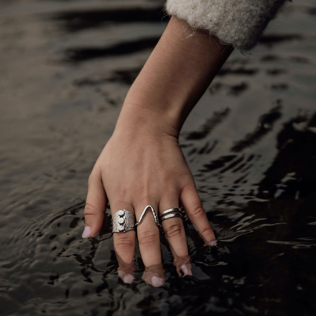 A woman dips her hand adorned with silver rings into a dark pool of water