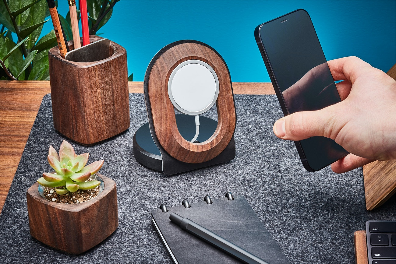 A hand holds a cell phone and wooden and wool office accessories sit on a wooden desk