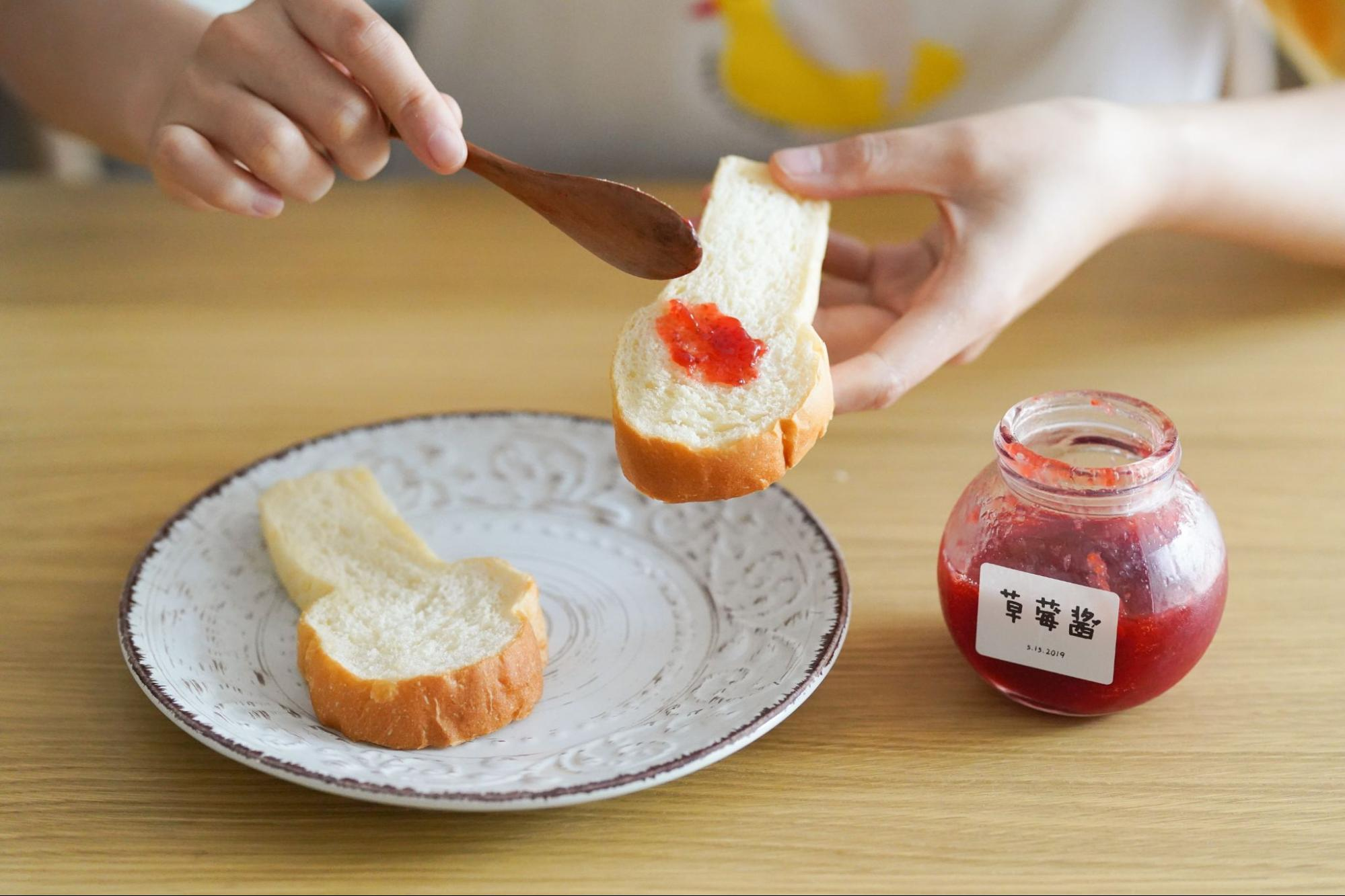 person-spreading-homemade-jam-on-bread