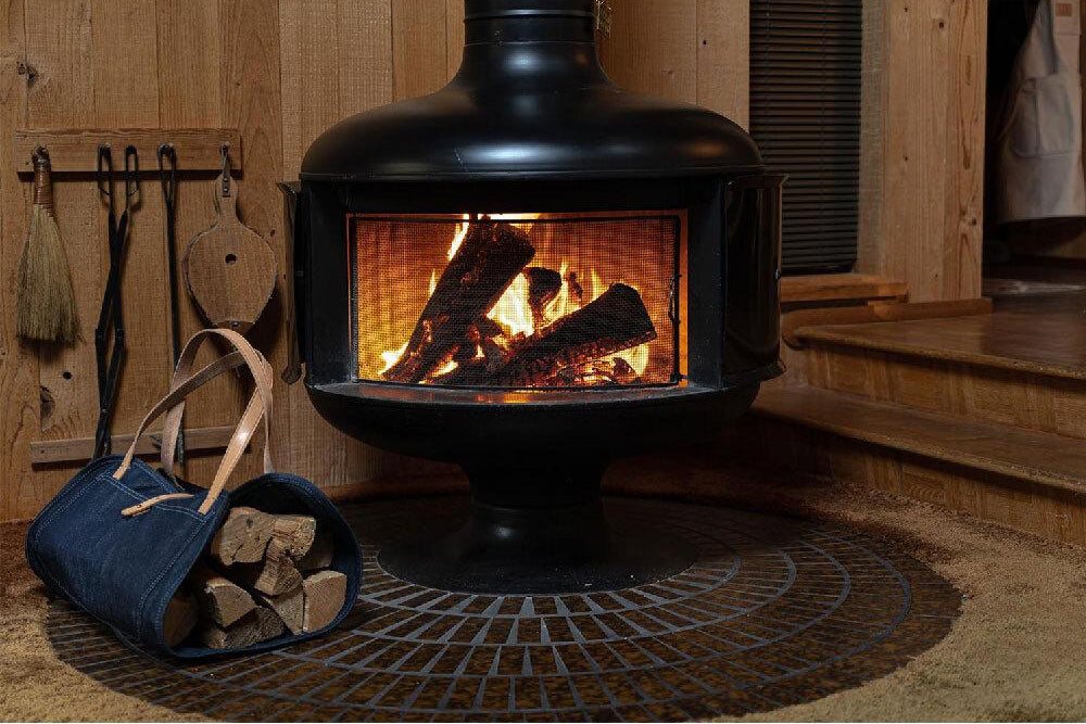 An indoor wood stove with a dire burning inside