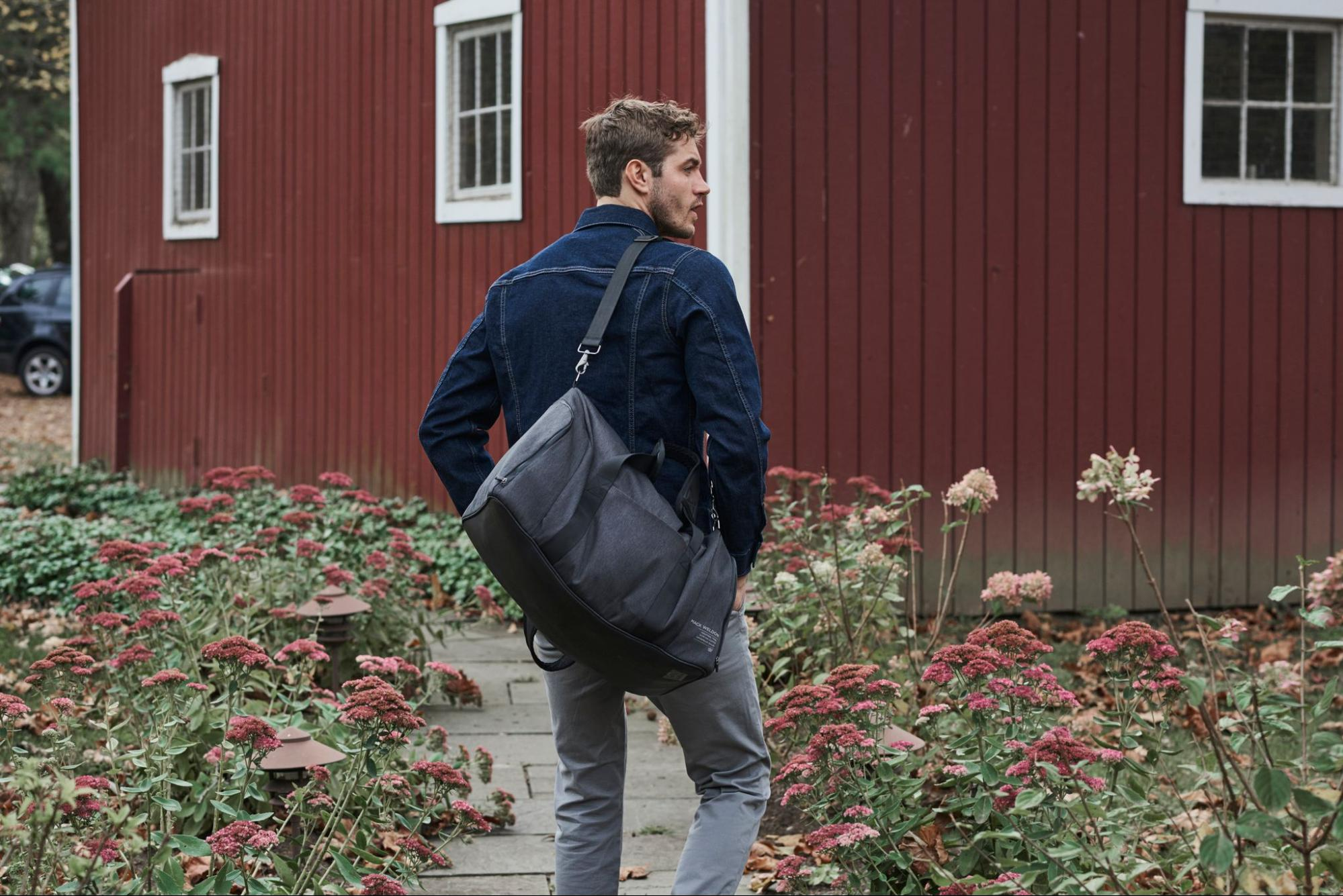 A model in a pair of jeans jacket and jeans carrying a weekender bag by Mack Weldon.