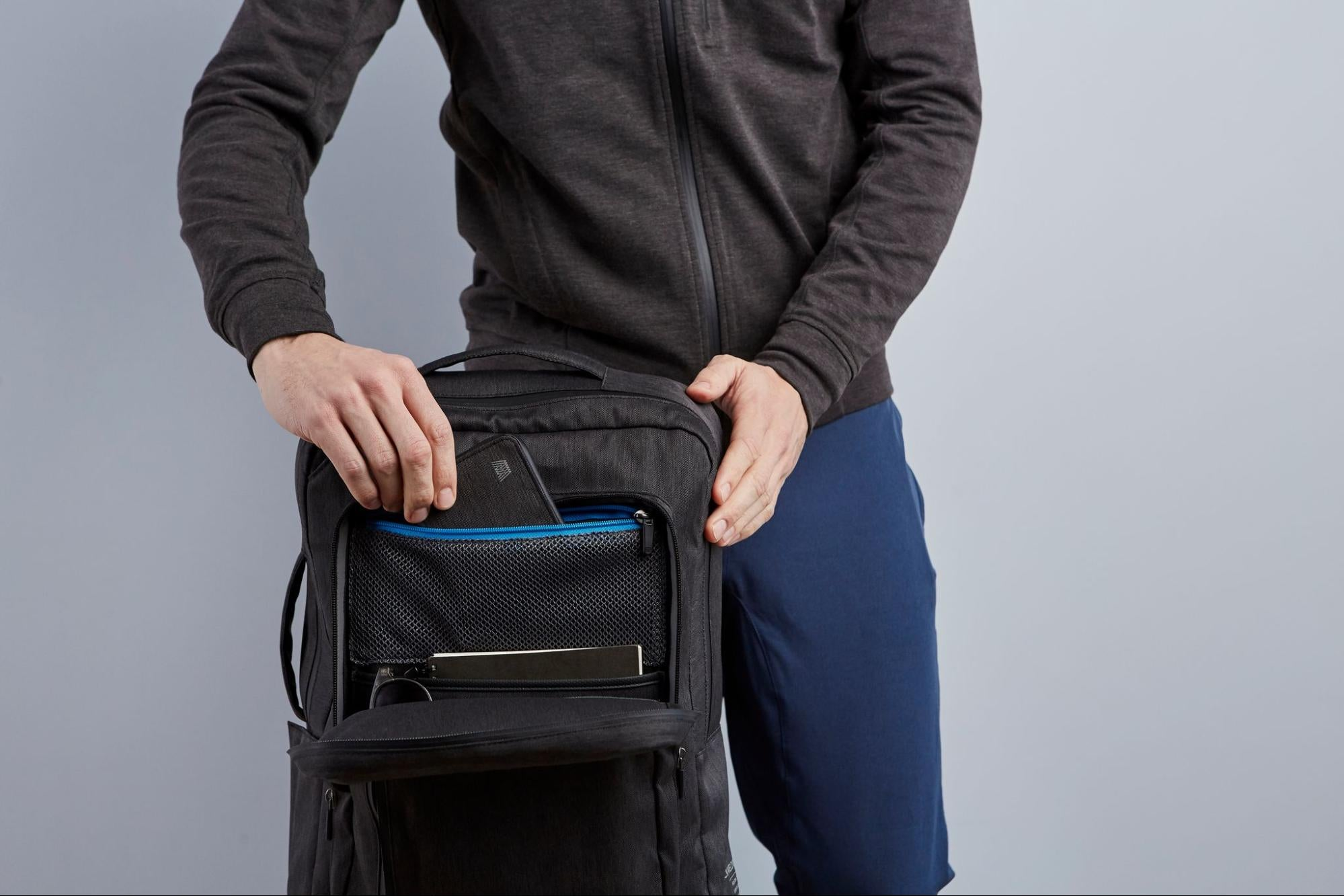 A model demonstrates some of the compartments within a travel pack from Mack Weldon.