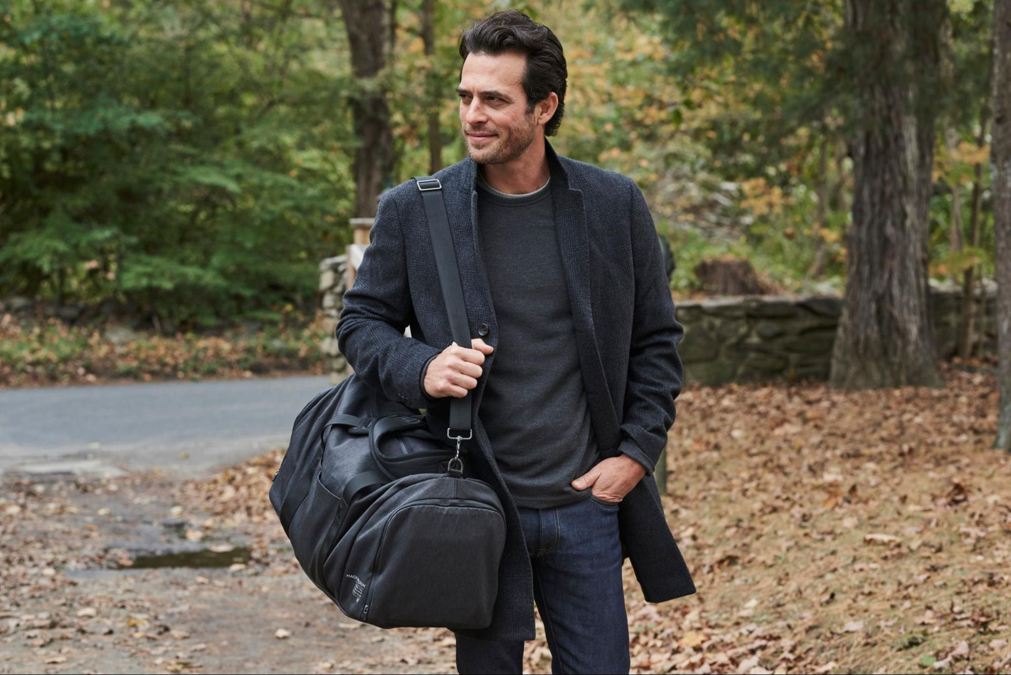 A model dressed in all gray, carrying the weekender tote by Mack Weldon.