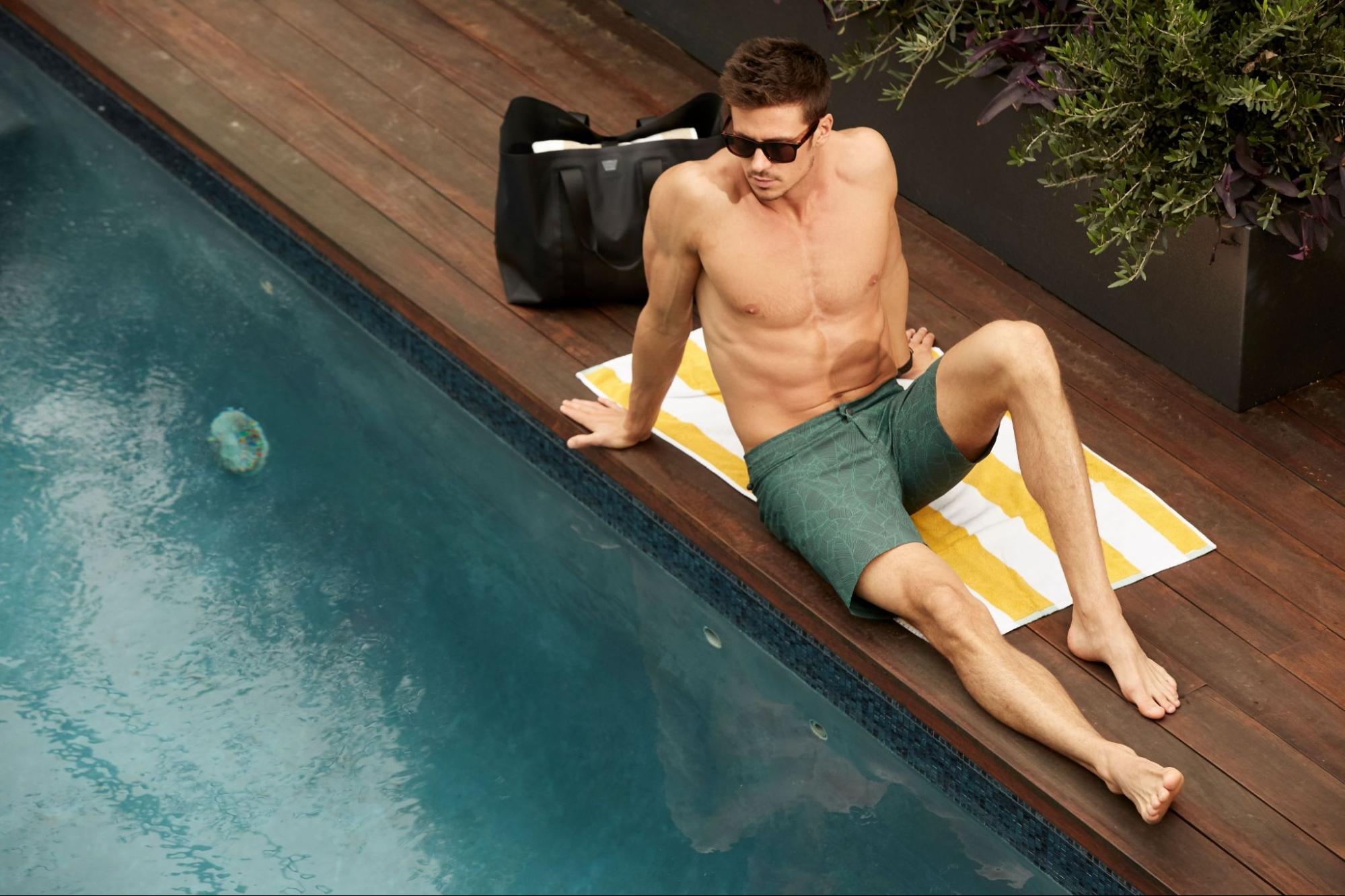 A model poses by a pool next to a travel tote by Mack Weldon.
