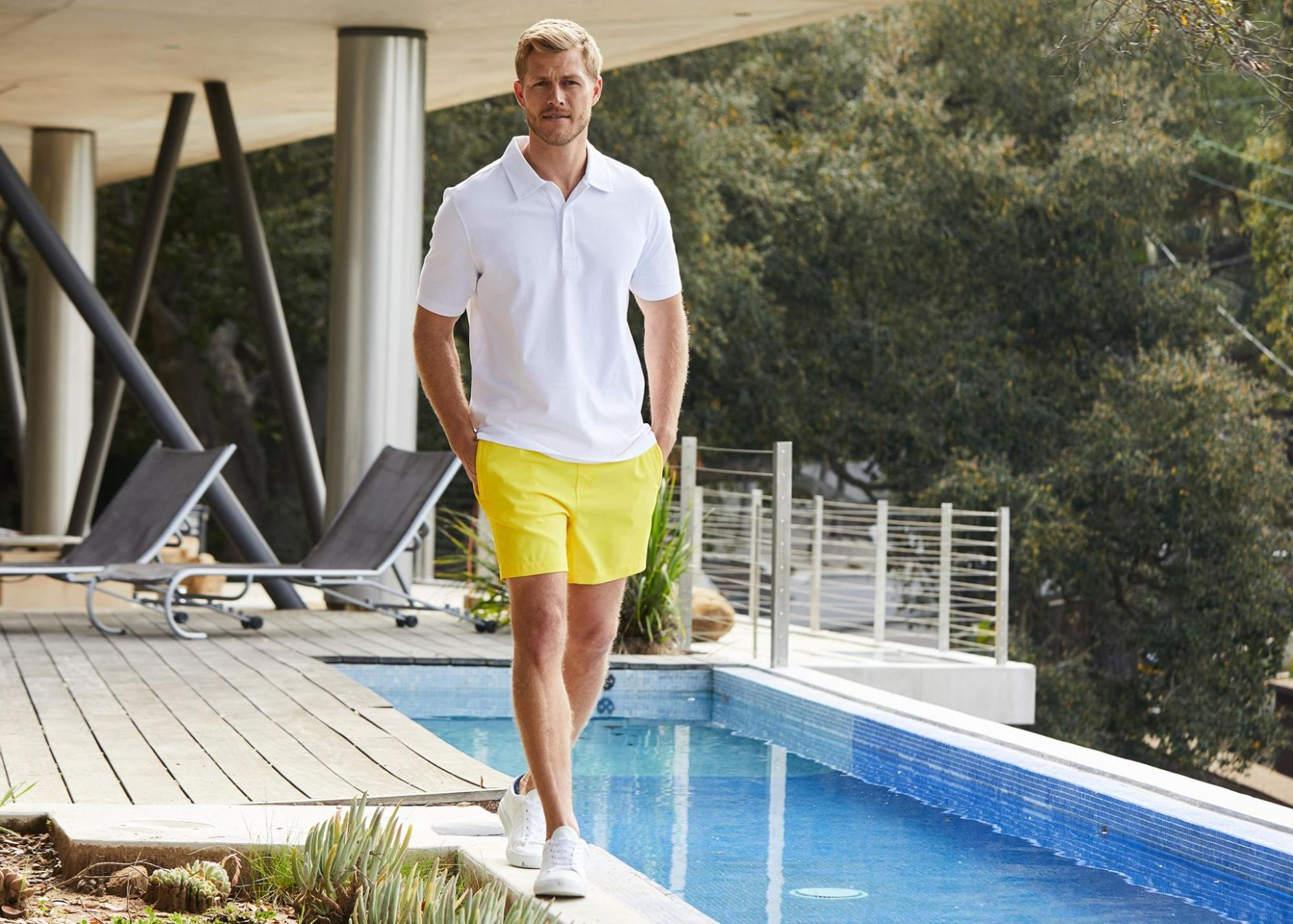 A male model in a white polo and yellow shorts standing next to a pool.