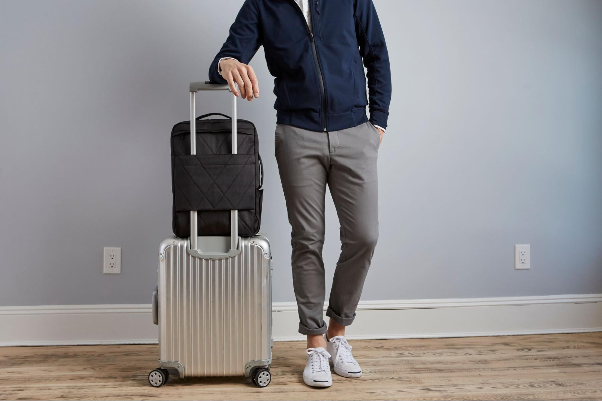 A model standing next to luggage and a travel pack from Mack Weldon.