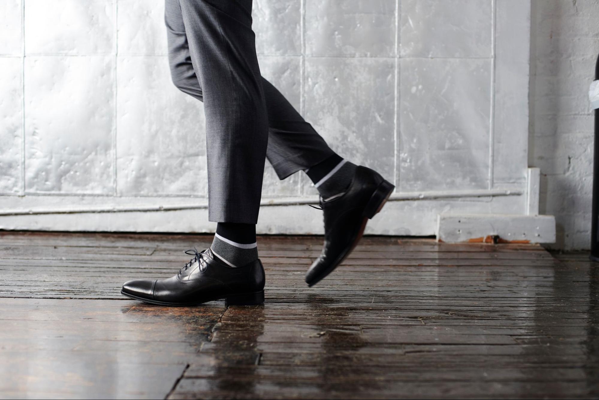 A pair of socks by Mack Weldon displayed on a model wearing leather shoes and dress pants.