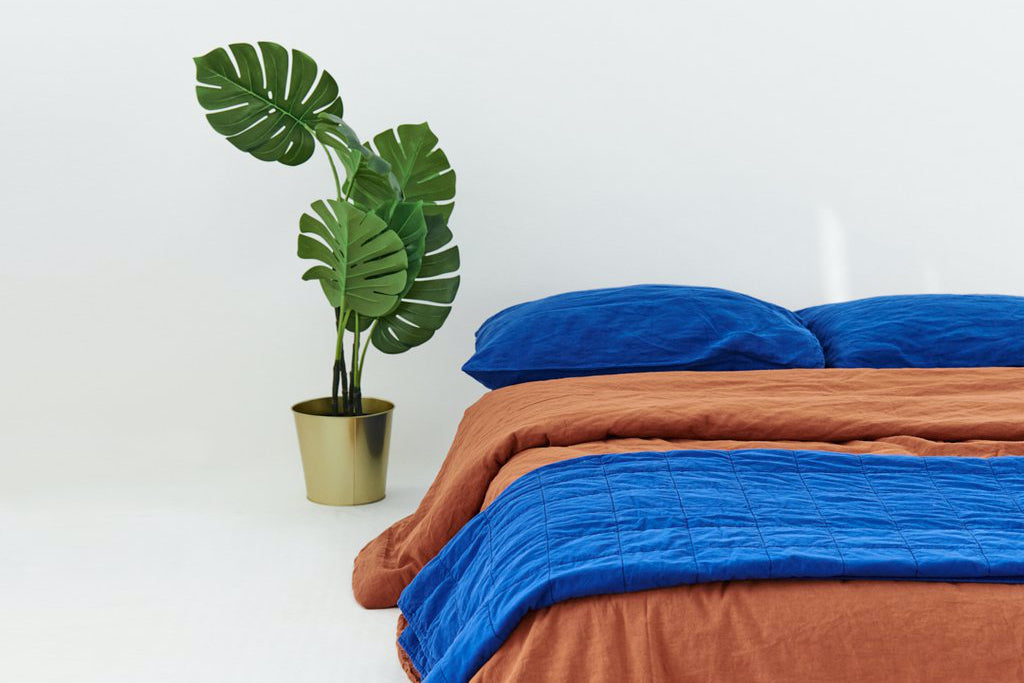A bed with bright blue and copper bedding