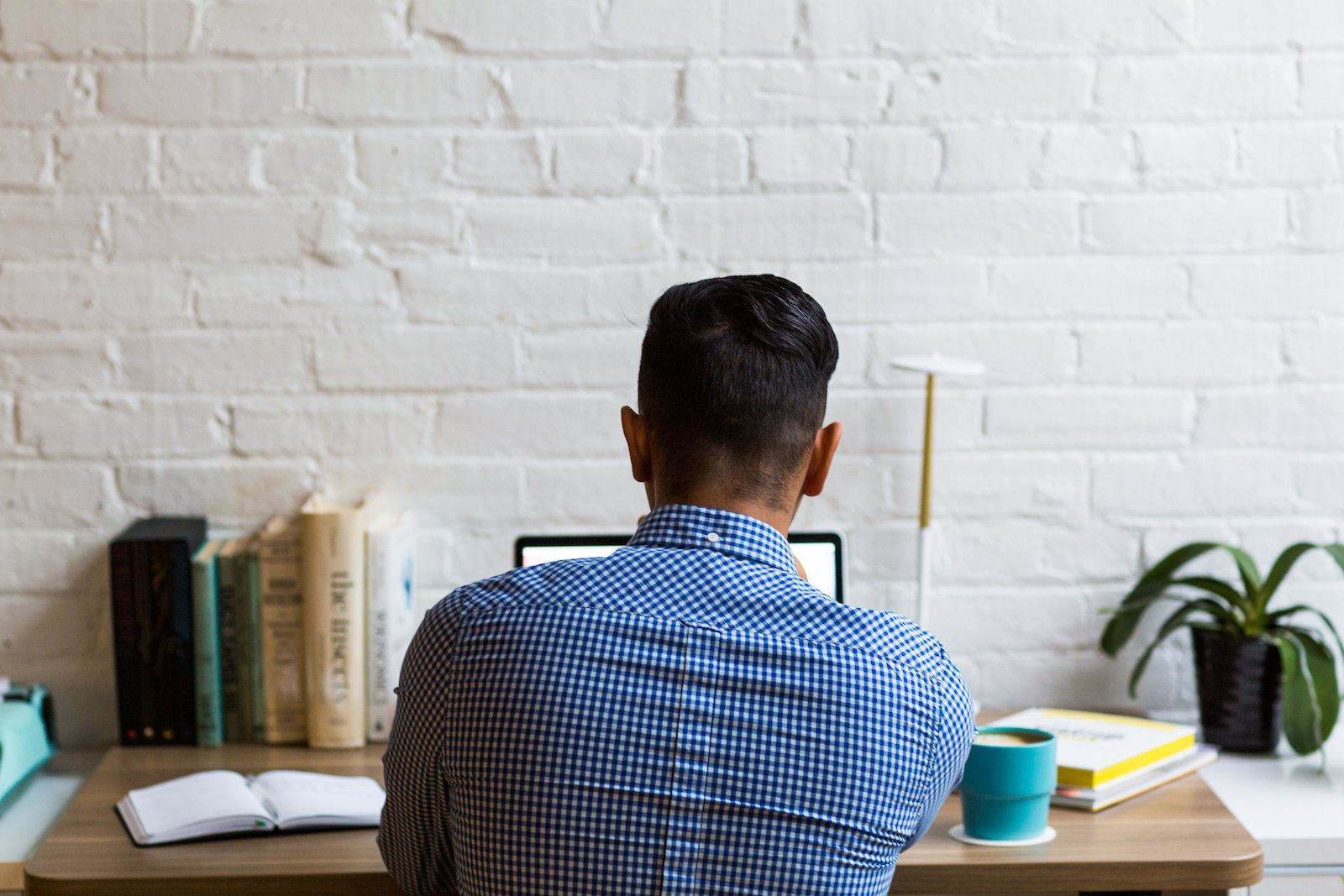 Image of a man sitting at a desk browsing the internet looking for business opportunities at home