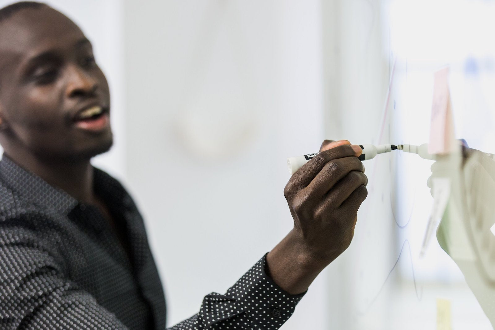 An image of a man writing his business opportunity ideas on a white board.
