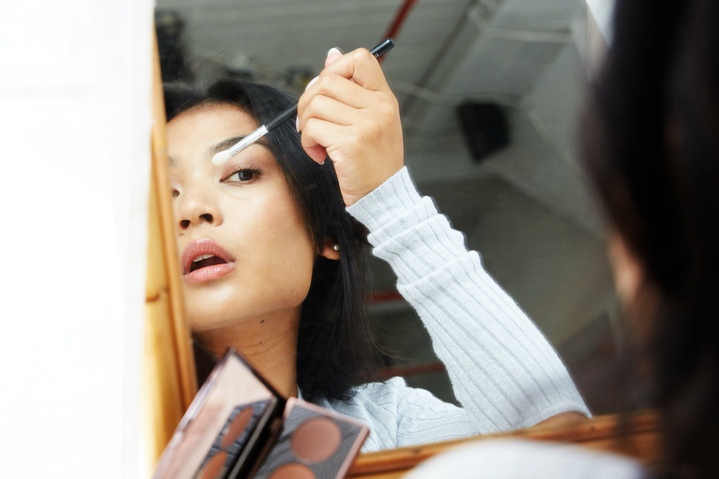 Image of a woman applying eye makeup in a mirror