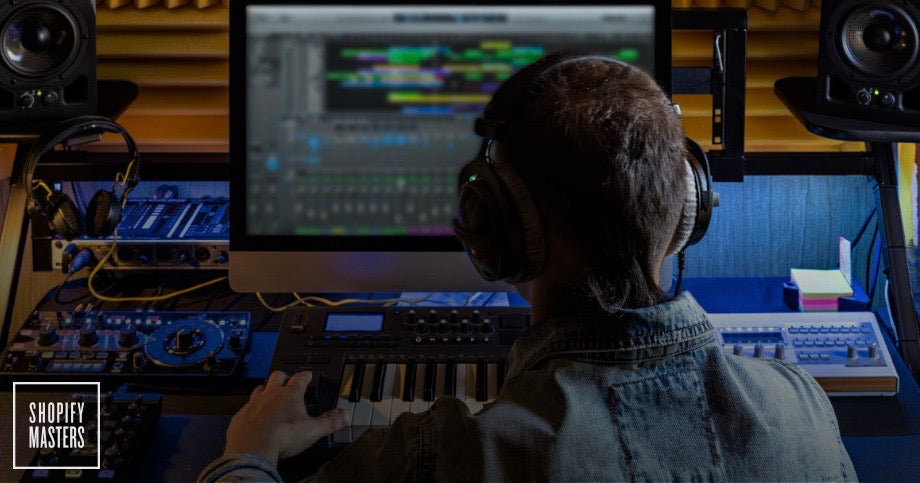 Production engineer edits music in front of a computer with headphones on.
