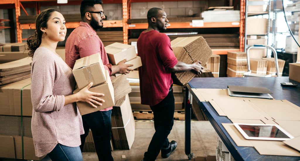 three people moving boxes in a warehouse