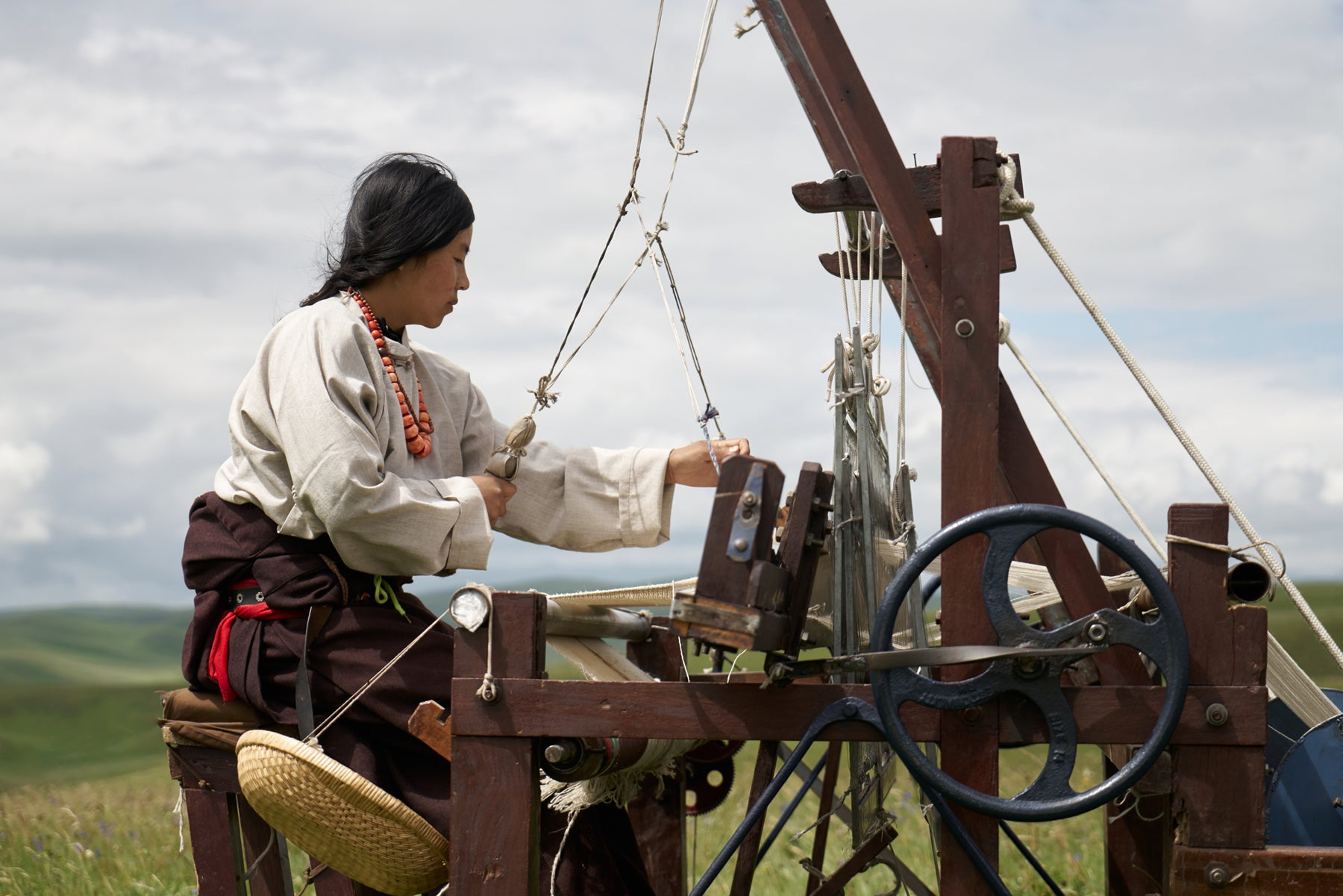 An artisan, in beige shirt and brown pants at an outdoor weaving machine, works on a piece of textile.