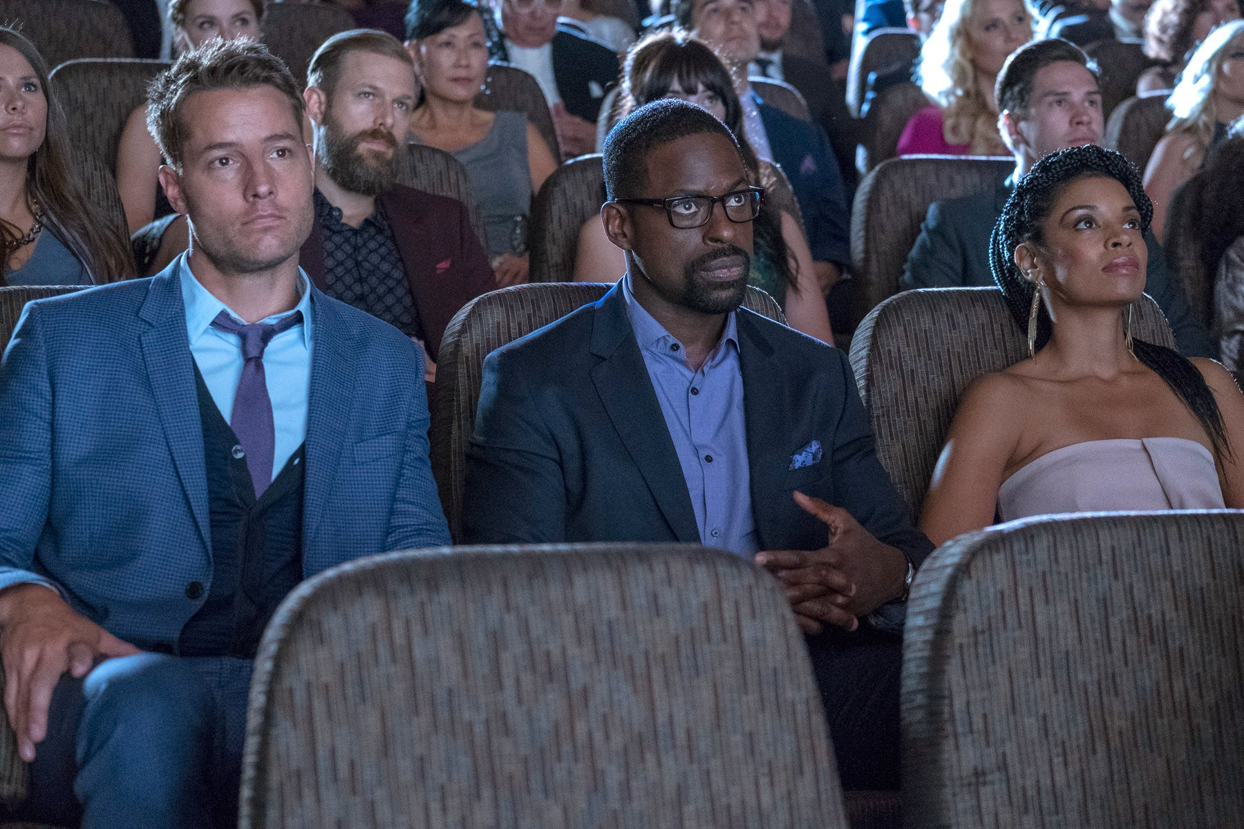 Kevin (Justin Hartley), Randall (Sterling K. Brown) ve Beth Pearson (Susan Kelechi Watson) This Is Us'un bir bölümünde karanlık ve kalabalık bir tiyatroda oturuyorlar.