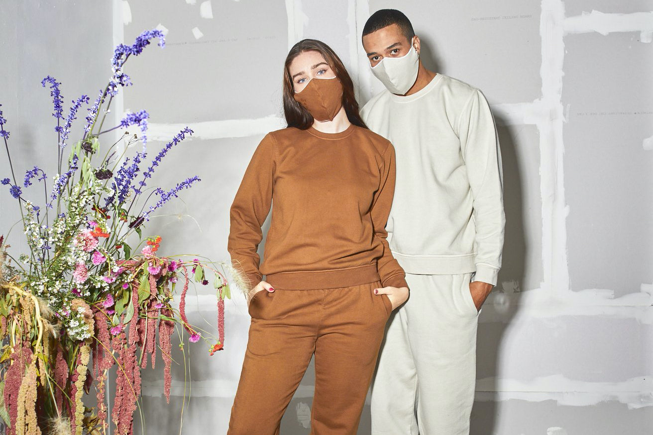 Two people model sweat suits and masks