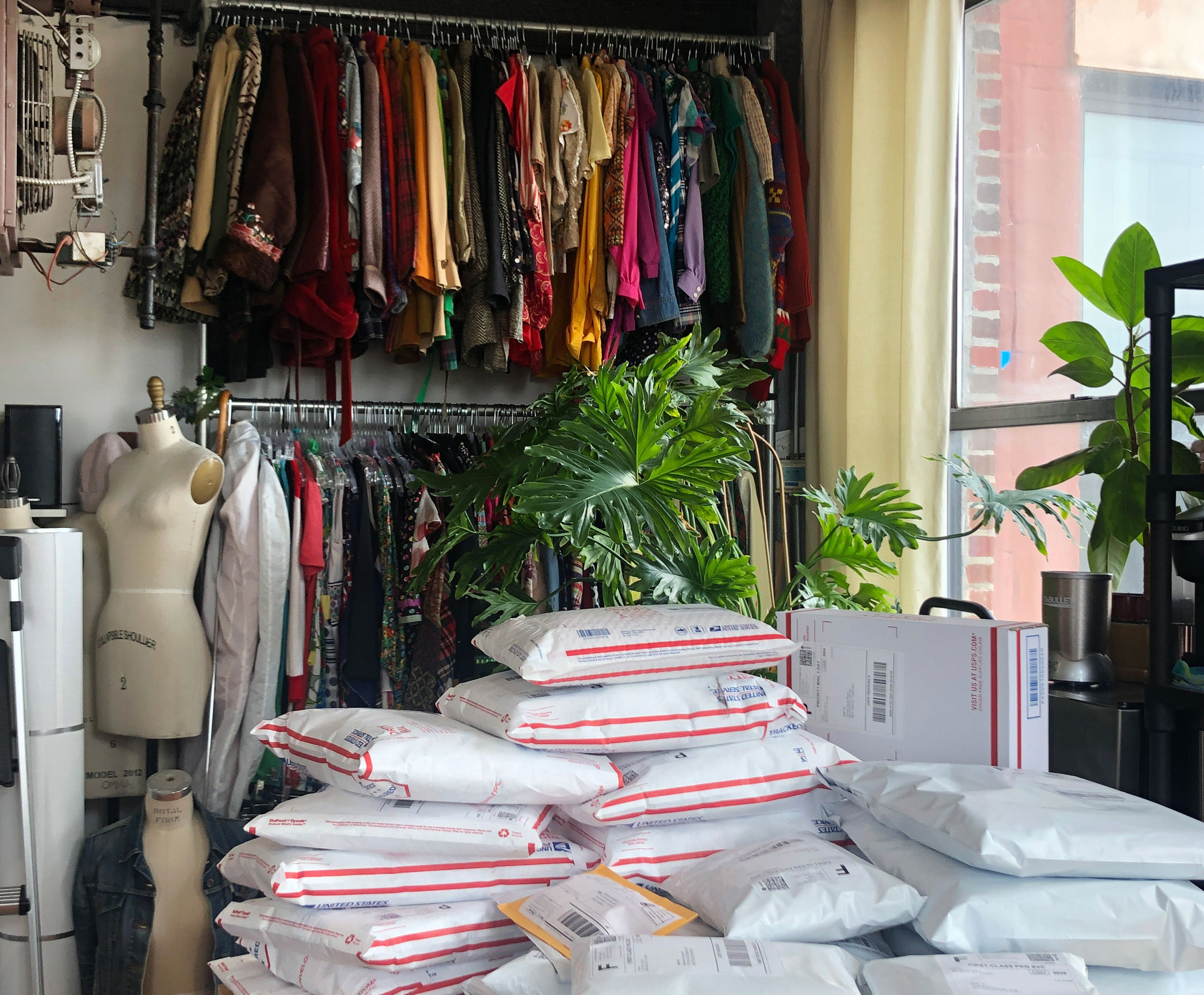 A store room filled with vintage clothing and packaged orders ready to be mailed