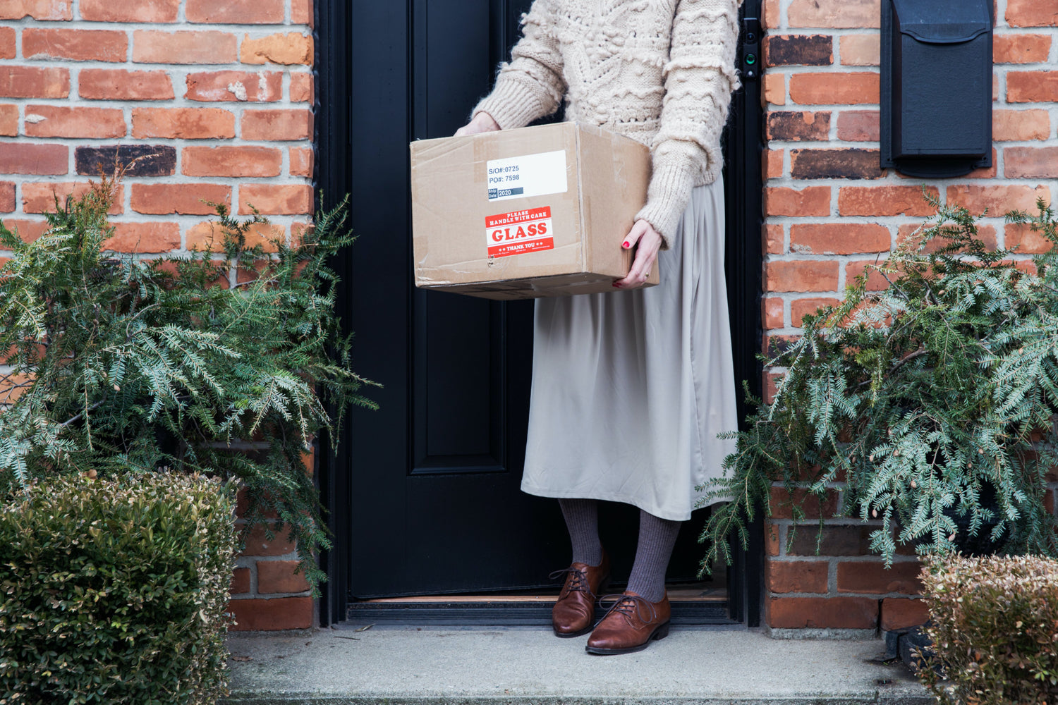 A woman holds a cardboard box on the front step of a brick house