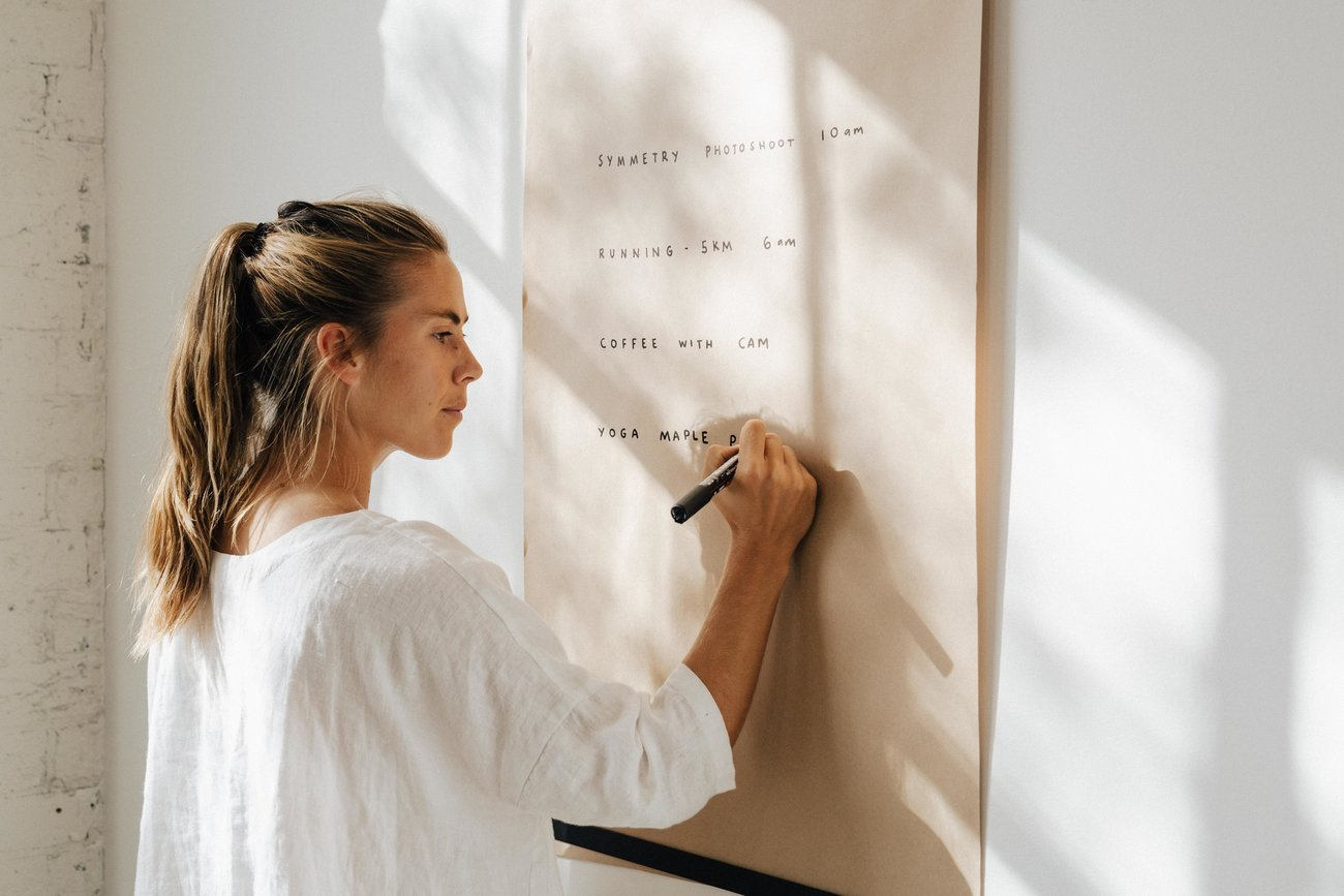 A woman writes on a large paper roller that is affixed to the wall