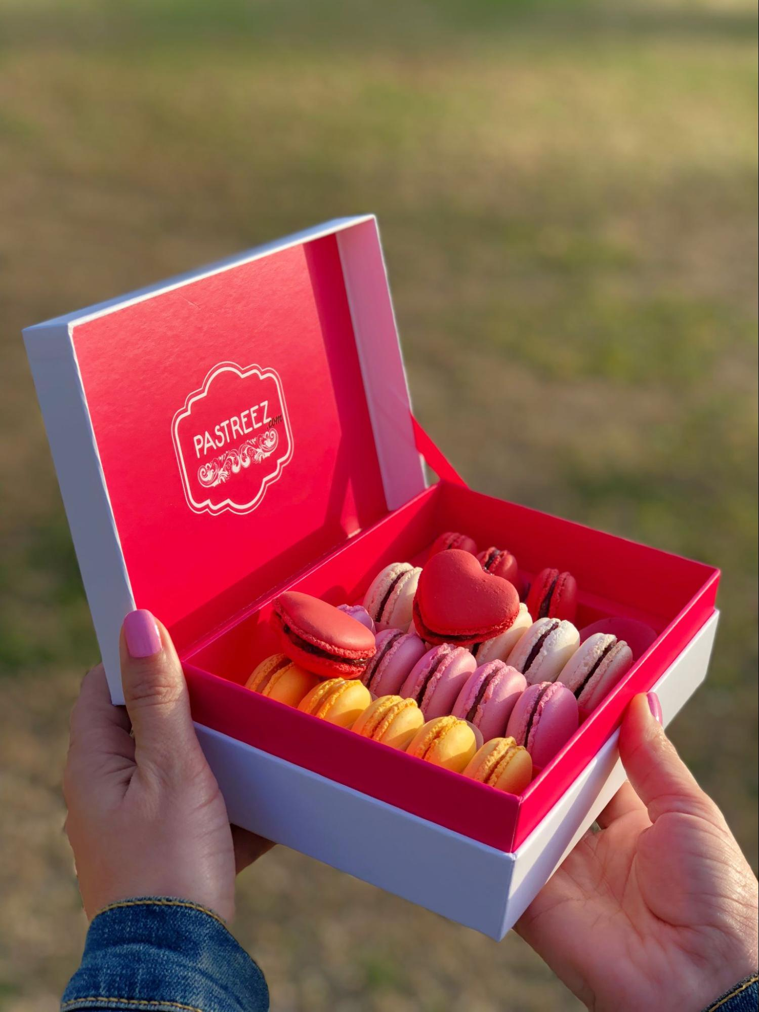A box of heart shaped macarons by Pastreez held by a hand model.