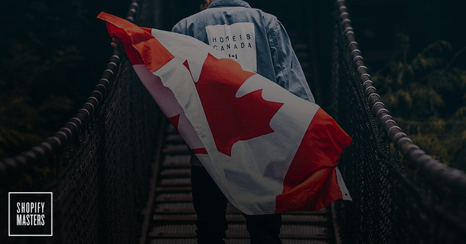 "Model wears a ""Home Is Canada"" jeans jacket while posing with a Canadian flag."