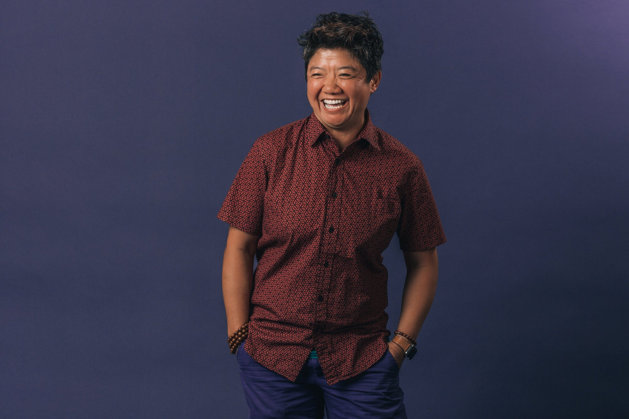 Portrait of a person laughing and standing in front of a dark blue background