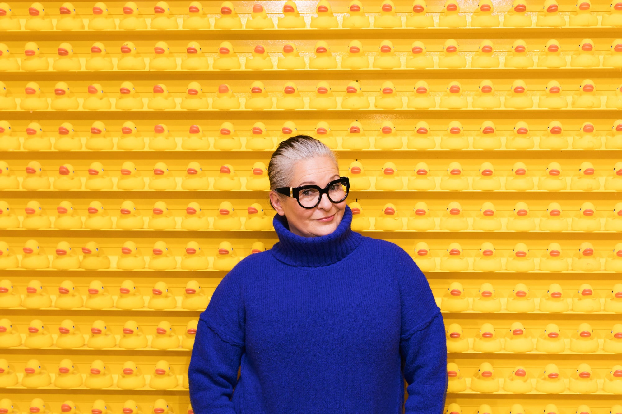 Portrait of an older woman against a yellow wall