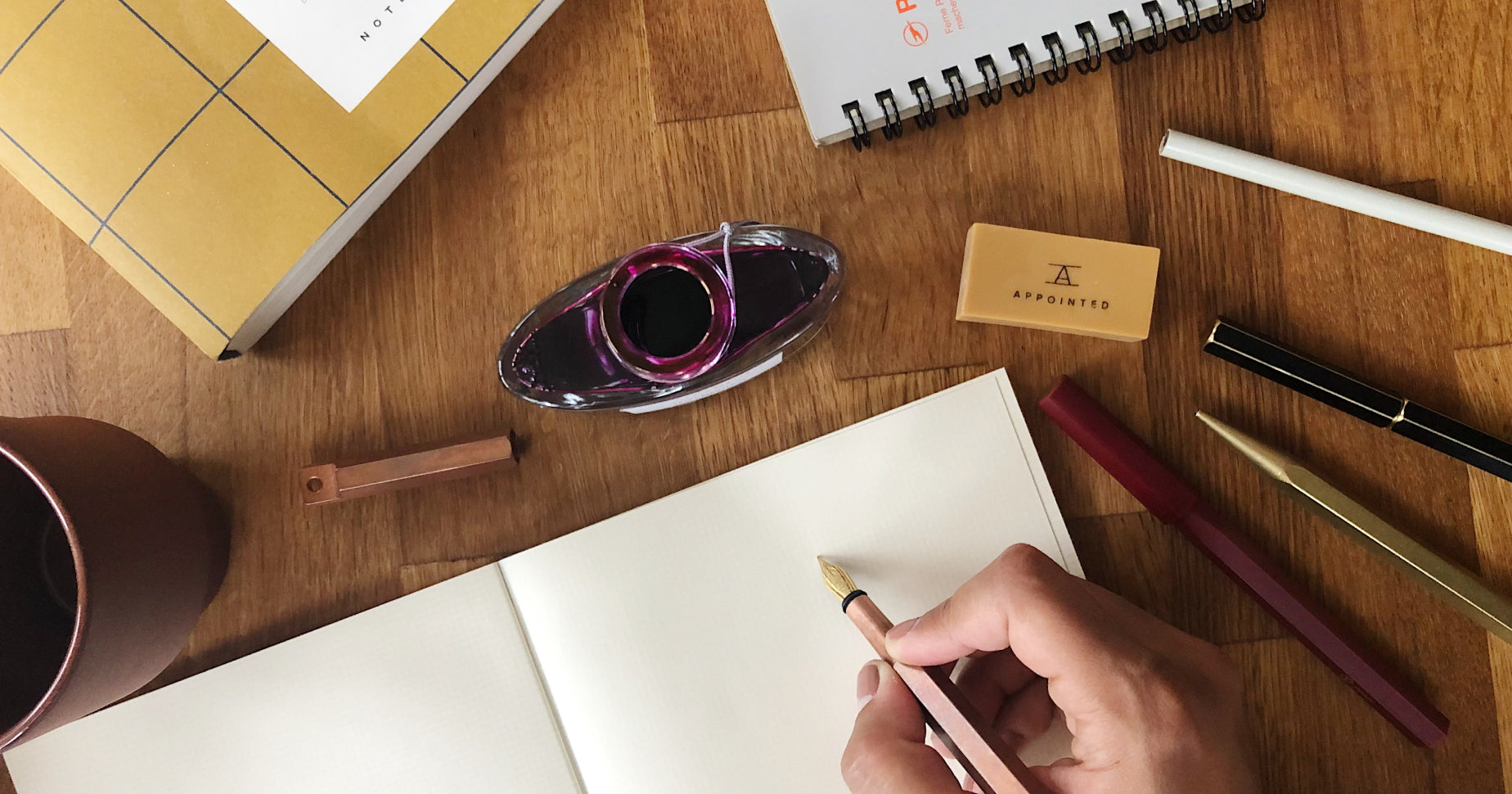 A hand gripping a fountain pen hovers above a blank notebook on a table. An inkwell, other pens, and some notebooks also rest on the table.